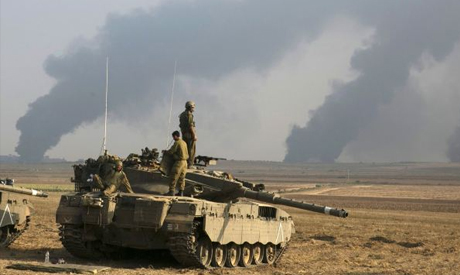 Israeli soldiers stand atop a tank