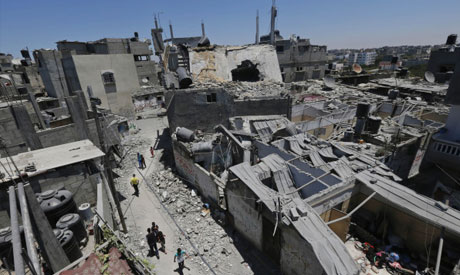 People walk through the site of an overnight Israeli strike at the Salahaldein mosque