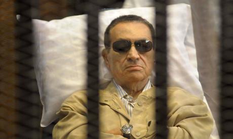 Hosni Mubarak sits inside a cage