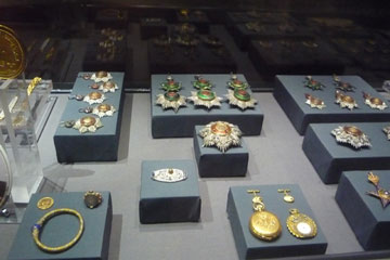 a collection of earrings, medallion and broock