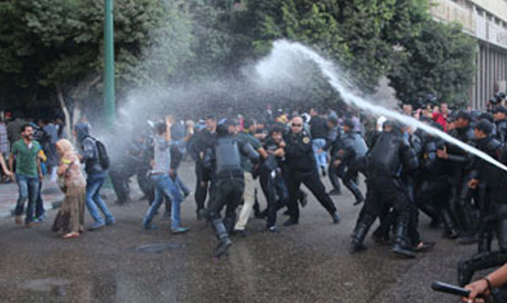 Egyptian policemen use a water canon to disperse protesters