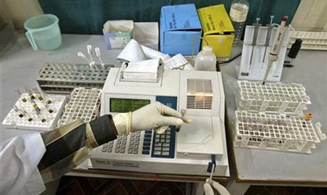 A laboratory assistant examines blood samples