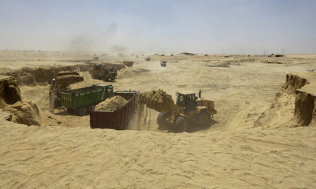 Bulldozers and trucks work on an upgrade project for the Suez Canal