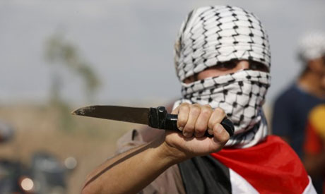 A masked Palestinian protester holds a knife