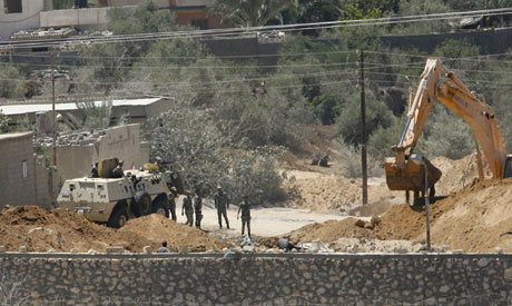 Egyptian soldiers secure the area as a bulldozer demolishes part of a smuggling tunnel on the Egypti