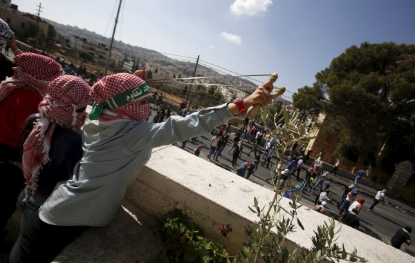 Palestinian woman throwing a stone