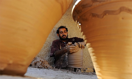 An Afghan potter works on a clay pot (AFP)