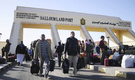 Egyptians cross from Libya to Egypt through the Salloum land port gate