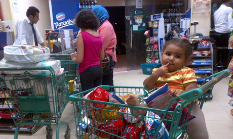A family buys groceries at a market,