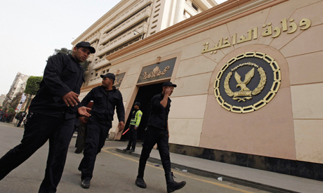 Riot police walk in front of the Interior Ministry headquarters in Cairo