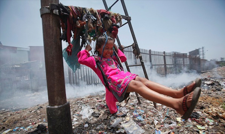 Kid playing near a a garbage dump