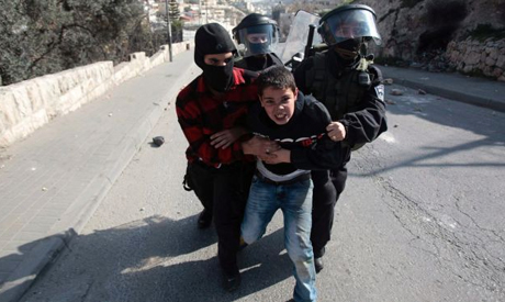 Israeli police officer and border police officers detain a Palestinian youth