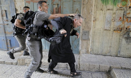 Israeli police officers detain a Palestinian protester