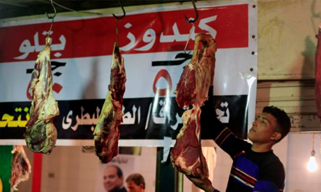 Egyptian butcher hangs meat at a market in Cairo