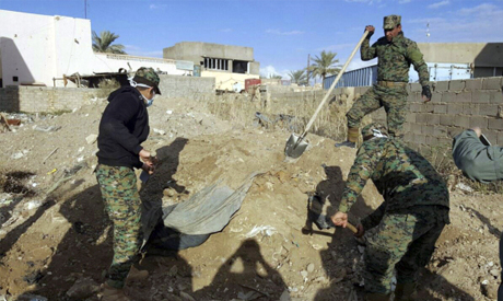 Iraqi security forces members work at the site of a mass grave