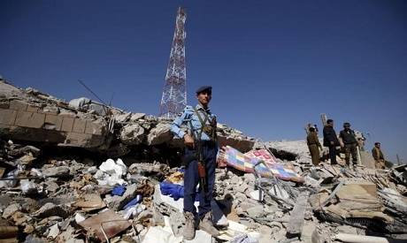 A policeman stands guard on the debris at the site of a Saudi-led air strike on the police headquart