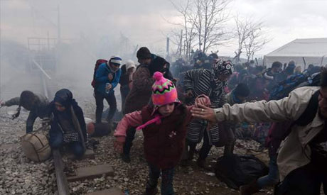 Refugees run away after Macedonian police officers fired tear gas
