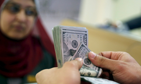 A customer counts his U.S. dollar notes in a bank in Cairo, Egypt, March 10, 2016 (Reuters)