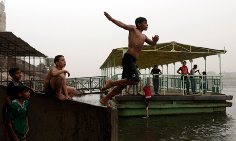 Children dive in the Nile to escape the hot weather during a heat wave in Cairo (Photo: Reuters)