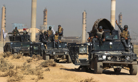 Iraqi forces drive past an oil production plant as they head towards the city of Kirkuk (Reuters)