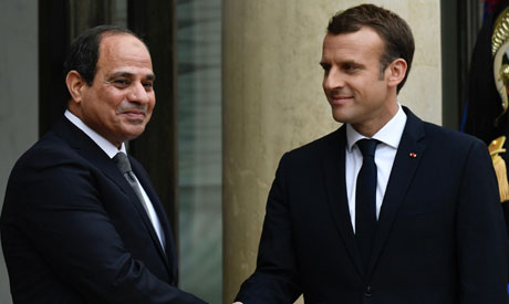 French President Emmanuel Macron (R) shakes hands with Egypt