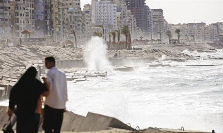 A couple walks near the shoreline in Alexandria (Reuters)