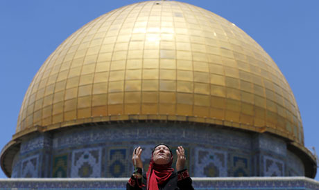 A Palestinian woman prays in front of the Dome of the Rock (Reuters)