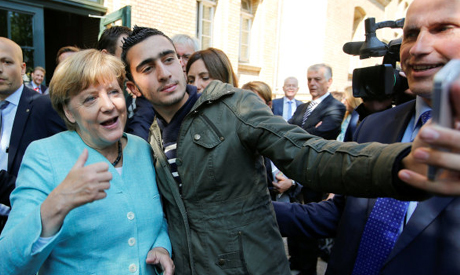 Syrian refugee Anas Modaman takes a selfie with German Chancellor Angela Merkel