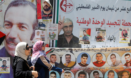 Women walk past pictures of Palestinian prisoners on hunger strike in Israeli jails, in the West Ban