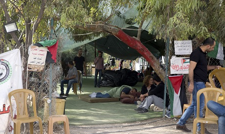 Palestinians activists sit in front of a tent for supporters of the West Bank Bedouin community of K