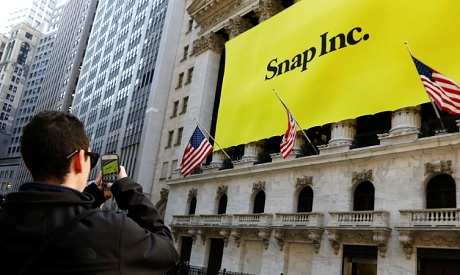 A man takes a photograph of the front of the New York Stock Exchange (NYSE) with a Snap Inc. logo hu