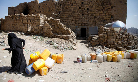A woman displaced from the Red Sea port city of Hodeidah pulls empty canisters outside her family sh