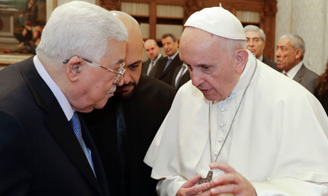 Pope Francis (R) speaks with Palestinian President Mahmoud Abbas at the end of a private audience at