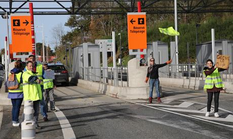 Demonstrators open the toll gates on motorway near Biarritz, southwestern France, Tuesday, Dec.4, 20