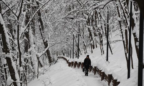 A woman walks through a snow covered alley after a snowstorm in Moscow, Russia (AP)