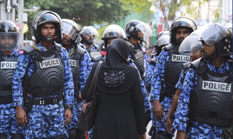 A Maldivian opposition supporter stands facing police