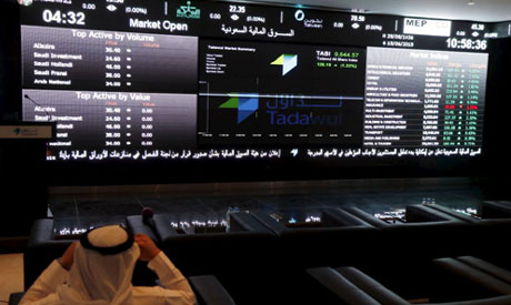 File photo: A trader monitors screens displaying stock information at the Saudi Stock Exchange. (Reu