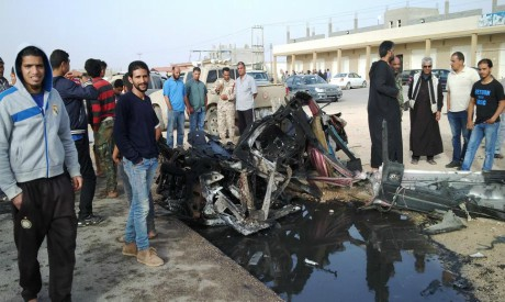 People inspect the site after a car bomb hit the convoy of Abdel-Razeq Nathouri, the chief of staff