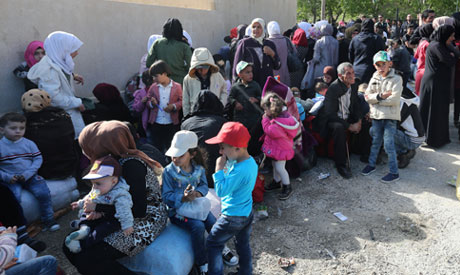 Syrian families who fled to Lebanon wait for buses to go back to Syria from the southern village of