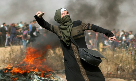 A girl hurls stones during clashes with Israeli troops at a protest where Palestinians demand the ri