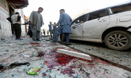 Afghan men inspect the site of a suicide bomb blast in Kabul, Afghanistan April 22, 2018