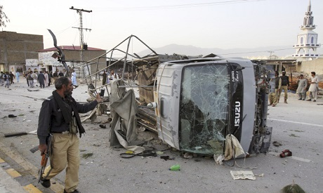 A Pakistani police officer walks past a police vehicle targeted by a suicide bomber in Quetta, Pakis
