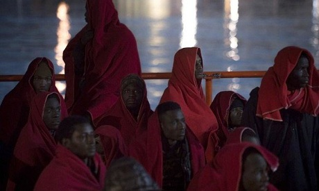 A group of migrants wrapped in Red Cross blankets arrive at the Spanish port of Malaga on board a Sp