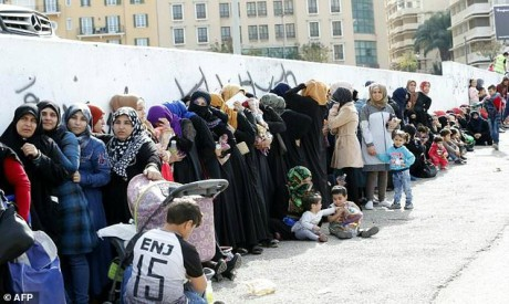 Syrian refugees queue to receive aid in Beirut