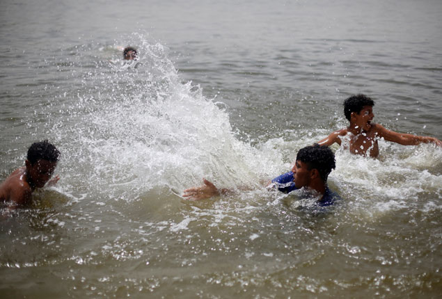 PHOTO GALLERY:  Egyptian boys run for the Nile to escape the hot and humid weather