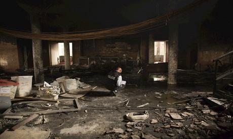 A police officer investigates damages at Libya