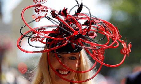 A racegoer poses before the start of the racing (Reuters)