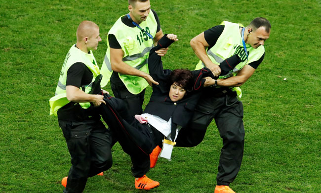 Stewards apprehend a pitch invader (Reuters)