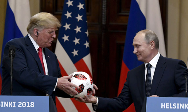 Russian President Vladimir Putin presents a soccer ball to U.S. President Donald Trump (AP)