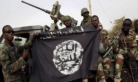 Reuters Nigerian soldiers hold up a Boko Haram flag that they seized in the retaken town of Damasak